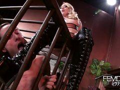 Заключенный в клетке раб лижет ноги своей сексуальной госпожи