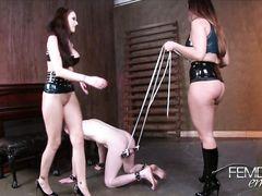 Домина растягивает мошонку бедного раба пока тот лижет пизду ее подруге