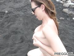 Беременная голая девушка на пляже обмазывает лечебной грязью