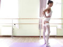 Миловидная гимнастка в чулках показывает растяжку