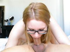 Старательная рыжая девушка сосет в очках член парня в позе 69