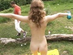 Голая гимнастка на природе делает зарядку и позирует без трусиков