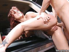 Рыжая девушка занимается анальным сексом в багажнике авто