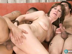 Пошлая зрелая женщина трахается с двумя парнями на диване