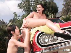 На капоте красного кабриолета юные азиатка и европейка предаются порочной лесбийской любви