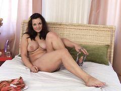 Полноватая девушка с красивой грудью мастурбирует вибратором в спальне