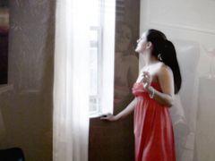 Сексуальная брюнетка позирует с сигаретой в платье