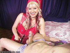 Госпожа в красном доминирует над парнем и сжимает его член щипцами