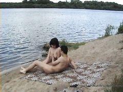 Обнаженные молодые нудисты ласкают друг друга на пляже