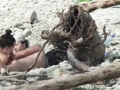 Отдыхающие нудисты на пляже не обращают внимание на камеру вуайериста